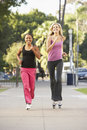 Two Female Friends Jogging On Street Royalty Free Stock Photography