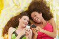 Two female friends lying on bed using mobile phones laughing Stock Photography