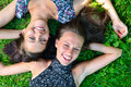 Two female friends is lying on grass Royalty Free Stock Photo