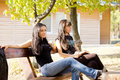 Two female friends sitting on a bench Stock Image