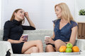 Two female friends talking and drinking tea together sitting on sofa during coffee break Royalty Free Stock Photo