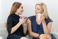 Two female friends talking and laughing together sitting on sofa during coffee break Royalty Free Stock Photo
