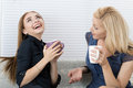 Two female friends talking and laughing together sitting on sofa during coffee break Stock Photo