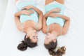 Two female friends in teal tank tops sleeping in bed Royalty Free Stock Photo