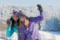 Two female friends winter snow in mountains enjoy holiday break Stock Photo