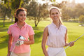 Two Female Golfers Walking Along Fairway Carrying Clubs Royalty Free Stock Photo