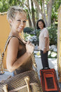 Two female holidaymakers with luggage happy multiethnic Royalty Free Stock Photos