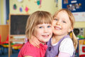 Two Female Pre School Pupils Hugging One Another Royalty Free Stock Photo
