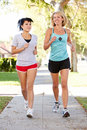 Two female runners exercising on suburban street running towards camera Stock Photos