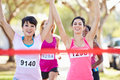 Two female runners finishing race together holding hands Royalty Free Stock Photo