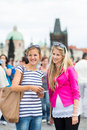 Two female tourists walking along the Charles Bridge Royalty Free Stock Image