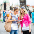 Two female tourists walking along the Charles Bridge while sight Stock Images