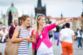 Two female tourists walking along the Charles Bridge while sight Royalty Free Stock Photo