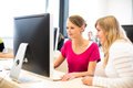 Two female universtiy/college students working on a desktop comp Royalty Free Stock Photo
