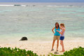 Two females on a beach walking the in rarotonga cook islands south pacific Royalty Free Stock Photos