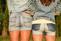 Two females in jeanswear outdoors jeans wear rear view close up Royalty Free Stock Image