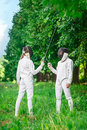 Two fencers women staying in park with crossed rapiers Royalty Free Stock Photo