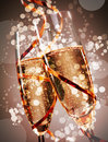 Two festive glasses of bubbly champagne flutes with sparkling bokeh wound round with a gold party streamer conceptual a wedding Stock Photo