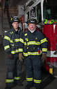 Two Firefighters Standing In Front of Fire Truck Royalty Free Stock Photos