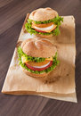 Two fish burgers on the wooden table Royalty Free Stock Photo