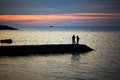 Two fishermen fish at sunset on the Black Sea Royalty Free Stock Photo
