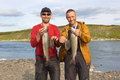 Two fishermen hold a huge graylings. Royalty Free Stock Photo