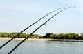 Two fishing rods black by the river Stock Image