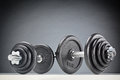 Two fitness dumbbells heavy next to each other on a white surface with gray background Royalty Free Stock Photo