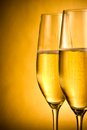 Two flutes of champagne with golden bubbles and space for text against background Stock Photography