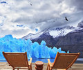 Two folding wooden chairs and perito moreno glacier a small bedside table on the boardwalk a comfortable place to enjoy the beauty Stock Photo