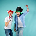 The two football fans with mouthpiece over blue background Royalty Free Stock Photography