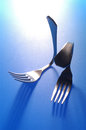 Two forks bent on blue background Royalty Free Stock Photo