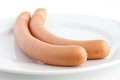 Two frankfurter sausages on a plate cooked with white background Royalty Free Stock Photos