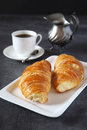 Two fresh croissants and cup of coffee on dark background Royalty Free Stock Photo