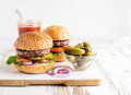 Two fresh homemade burgers, pickles, ketchup and onion rings on white wooden serving board Royalty Free Stock Photo