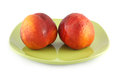 Two fresh peach on a green plate Royalty Free Stock Photo