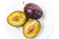 Two fresh plums black plum white plate Royalty Free Stock Photo