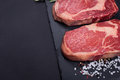 Two fresh raw marble meat, black Angus ribeye steak with spices on a dark stone background. Royalty Free Stock Photo