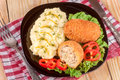 Two fried breaded cutlet with mashed potatoes and lettuce on a black plate wooden background Royalty Free Stock Photo
