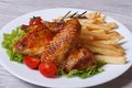 Two fried chicken wings with a crispy crust and fries on plate Royalty Free Stock Images