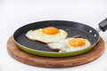 Two fried eggs in a frying pan on a kitchen wooden board Royalty Free Stock Photo