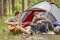 Two friend sitting in the tent play the guitar and sing songs young Stock Photo
