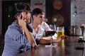Two friends at the bar with a woman on a mobile relaxing together drinking women talking phone serious expression and large Royalty Free Stock Photos