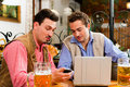 Two friends in Bavarian pub with laptop Stock Images