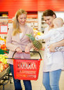 Two Friends Buying Groceries with Baby Royalty Free Stock Photos
