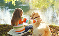 Two friends, child with Labrador retriever dog sitting in summer