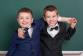 Two friends, elementary school boy near blank chalkboard background, dressed in classic black suit, group pupil, education concept Royalty Free Stock Photo