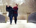 Two friends enjoying their walk at the park cheerful strolling in cold winter Royalty Free Stock Photo