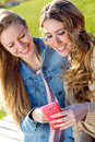 Two friends having fun with smartphones in the street Royalty Free Stock Photography