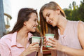 Two friends hawing a coffeebreak attractive girls outdoors Stock Image